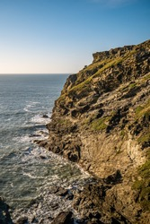 Rocky coastline at Tintagel in North Devon. Tintagel castle surroundings. Clear sky, sunny day, idilic and beautiful coastline. Taken in Portrait.
