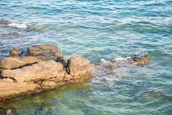 Rocky coastline. coastline with water swirling around the rocks.