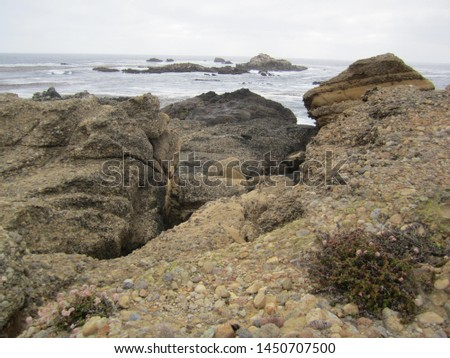 Rocky coastline of California's central coast along the Pacific Ocean on a cloudy day.