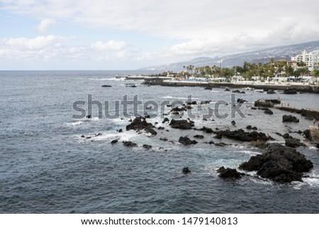 Rocky coastline with city on background #1479140813