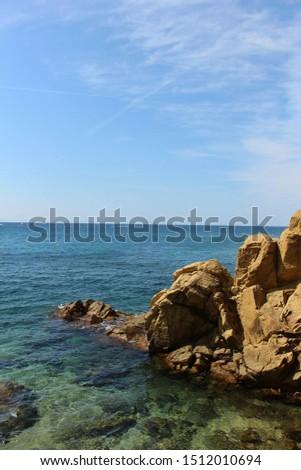 Rocky coastline with clear azure blue water, Mediterranean Sea, Catalonia, Lloret de Mar near Barcelona