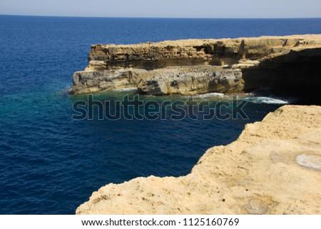 Rocky coastline with clear blue water in the ocean in Gozo, Malta in Europe #1125160769
