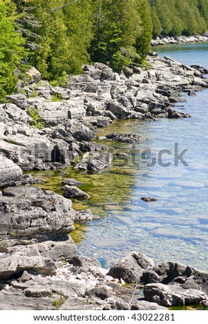 Rocky coastline with evergreen trees lining the water's edge, in the Bruce Peninsula, on Georgian Bay, Ontario.