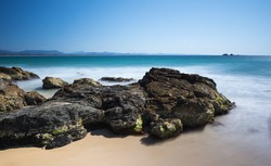 Rocky Coastline With Sand And Misty Ocean Below The Cape Byron Lighthouse And Overlooking the Julian Rocks Island with a Beautiful Clear Blue Sky, Wategos Beach, Byron Bay, New South Wales, Australia