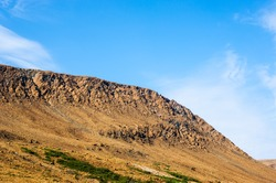 Rocky dry yellow cliff sloping down, against light blue sky, at Tablelands, Gros Morne National Park, Newfoundland, Canada.