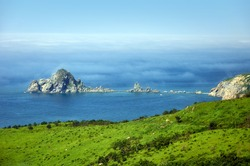 Rocky island in the sea in the fog during the day.