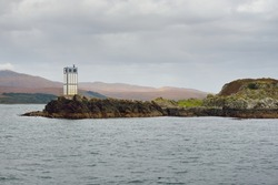 Rocky lake shore, mountain peaks, mountains, valleys and hills. Lighthouse. Panoramic view from a sailboat. Dramatic sky. Scotland, UK. Atmospheric landscape. Travel destinations, hiking, ecotourism