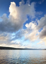 Rocky lake shores under the colorful evening sky after the rain. Dramatic cloudscape. Gare Loch, Rhu, Scotland, UK
