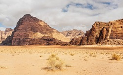 Rocky massifs on red sand desert, few dry grass cluster ground, cloudy sky in background, typical scenery in Wadi Rum, Jordan