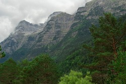 Rocky mountain chain covered with green forests in Bielsa, Huesca, Aragon, Spain. Alpine landscape in Ordesa and Monte Perdido national park, in the Spanish Pyrenees.
