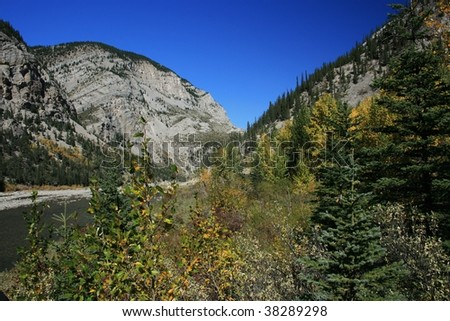 Rocky mountain outlined against bright blue sky; fall foliage in foreground; river between; Oldman River, Alberta, Canada