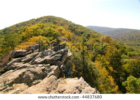 rocky mountain peak and view of an autumn valley - stock photo