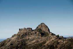 Rocky mountain peak at a mountain ridge under a clear blue sky