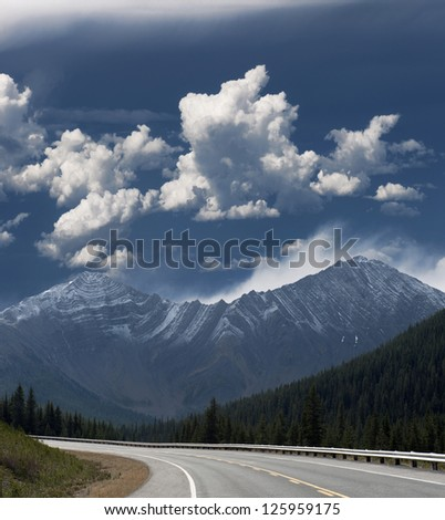 Rocky Mountains - highway, mountains and cloudy sky