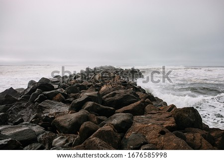 Rocky pier in pacific ocean. Pacific Northwest. Rocky breakwater. Birds resting on the breakwater.