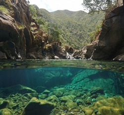 Rocky river with clear water, split view over and under water surface, Oceania, New Caledonia, Dumbea