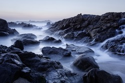 Rocky sea beach at dusk, last sun rays, seeing a salt water cascade during low tide. North of Portugal. Long exposure.