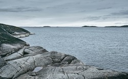 Rocky sea shore on an overcast day. Scenic view. Background for travel layouts. Blue and grey backdrop