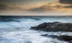 Rocky seashore with wavy ocean and waves crashing on the rocks at sunset. Larnaca coast area in Limassol, Cyprus