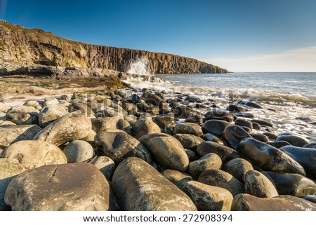 Rocky shore at Cullernose Point / Waves crashing against the rocks at Cullernose Point with sea washed boulders in the foreground