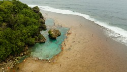Rocky shore at low tide with swimming pools and tourists. Magpupungko natural rock pools. Siargao, Philippines.