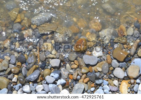 Rocky shore close up.  Small rocks and stones along a fresh water creek.  Bright macro image with varying rough and smooth textures.  Wet pebbles glimmering in the water.  Pushing and pulling stones