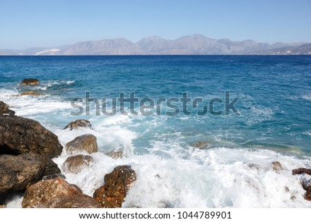 Rocky shore with mountains in the background. The spray of the surf #1044789901