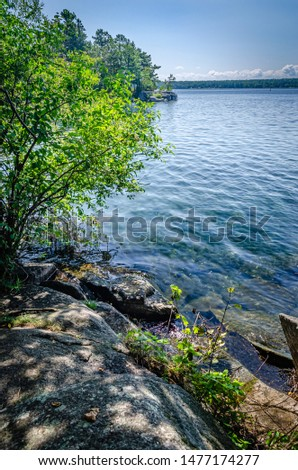Rocky shoreline in the Thousand Islands, St. Lawrence River with clouds on the horizon