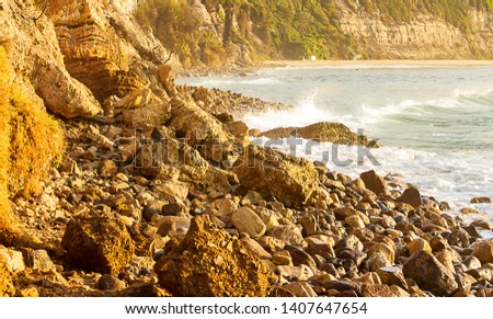 Rocky shoreline with cliff, wave breaking through bay