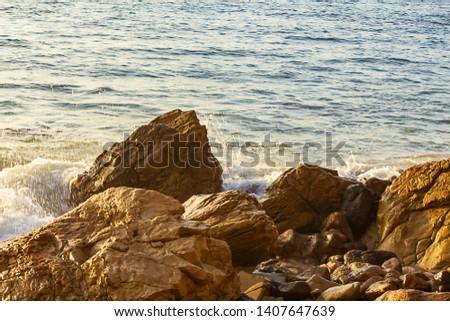 rocky shoreline with water swirl and open ocean texture