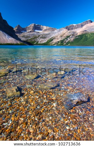 Rocky substrate visible under clear waters of Bow Lake in Banff National Park of Canada