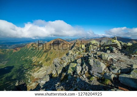 rocky Tatra mountain tourist hiking trails under blue sky and occasional mist  cloud in Slovakia, path to Volovec mountain