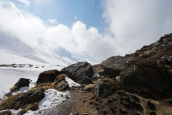 Rocky trail steps with snowy mountain cliff and cloudy blue sky