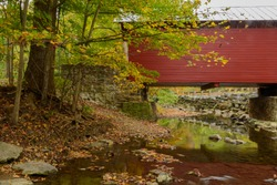Roddy Road covered bridge is a majestic red color crossing over a stream. Autumn colors are turning in contrast to the red wood of the bridge near Thurmont MD.