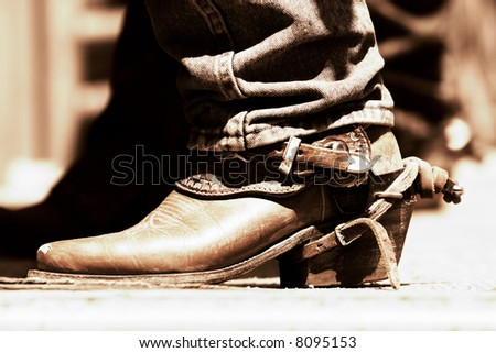 Rodeo Cowboy Boot and Spur in sunlight and shadow with high contrast copper tone (shallow focus).