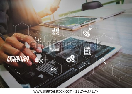 ROI Return on Investment indicator in virtual dashboard for improving business. Businessman hand touching digital tablet.Photo finance manager working new Investment project office.