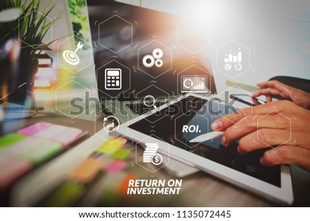 ROI Return on Investment indicator in virtual dashboard for improving business. businessman working with blank screen digital tablet computer and smart phone and laptop computer on wooden desk.