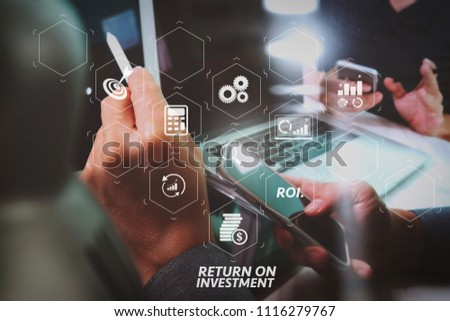 ROI Return on Investment indicator in virtual dashboard for improving business. website graphic designer hand working with his team make new project in studio. #1116279767