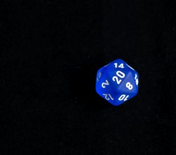 Role playing die showing a natural 20 roll on a d20 form a set of dice - set to the side for easy addition of wording