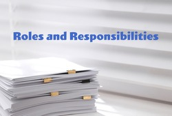 Roles and Responsibilities concept. Stack of paper on window sill indoors