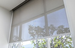 Roll Blinds on the windows, the sun does not penetrate the house. Window in the Interior Roller Blinds. Beautiful Blinds on the Window, the Sun and Heat Protection, the Perfect Windows Interior Decor