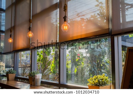 Shutterstock roll blinds to protect sunlight and lighting to decorate the coffee shop.