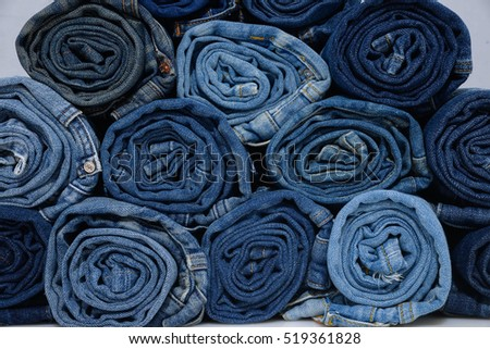 roll blue denim jeans arranged in stack-gray background
