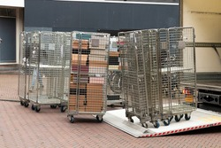Roll containers or roll cage trolleys  on the road unloaded from a truck with open flap.