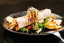 Roll filled with pulled pork meat with green salad and chips on dark background
