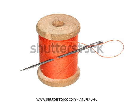 Roll of a thread and needle on a white background.