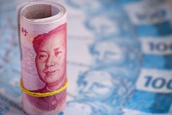 roll of banknotes of 100 yuan, with banknotes of 100 reais from brazil in the blurred background. Chinese market valuation and its Renminbi currency