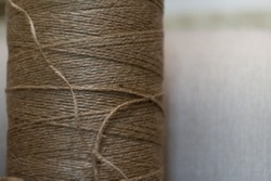 roll of natural rope, brown rope on light background, natural thread for handmade, brown tones in vintage style, garment factory