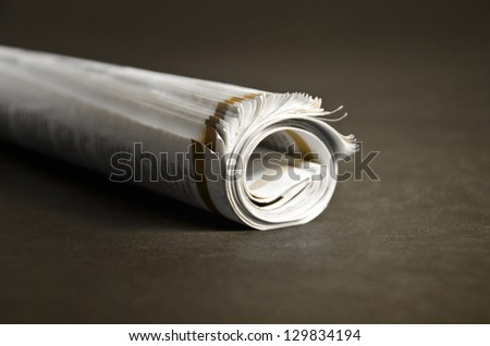 Roll of newspapers isolated on dark background. Selective focus.