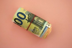 Roll of one hundred euro banknotes (with 50 and 20 euros inside) with red rubber band. Money/finance at pink background
